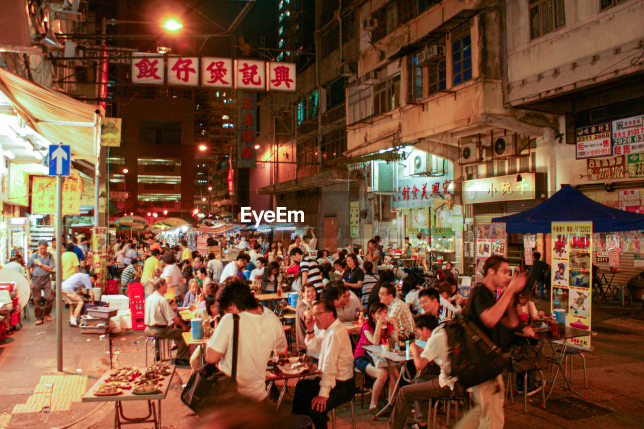 group of people, large group of people, city, crowd, illuminated, architecture, building exterior, table, city life, night, women, street, text, real people, adult, restaurant, men, sitting, built structure, sign, neon, outdoors, dining, nightlife