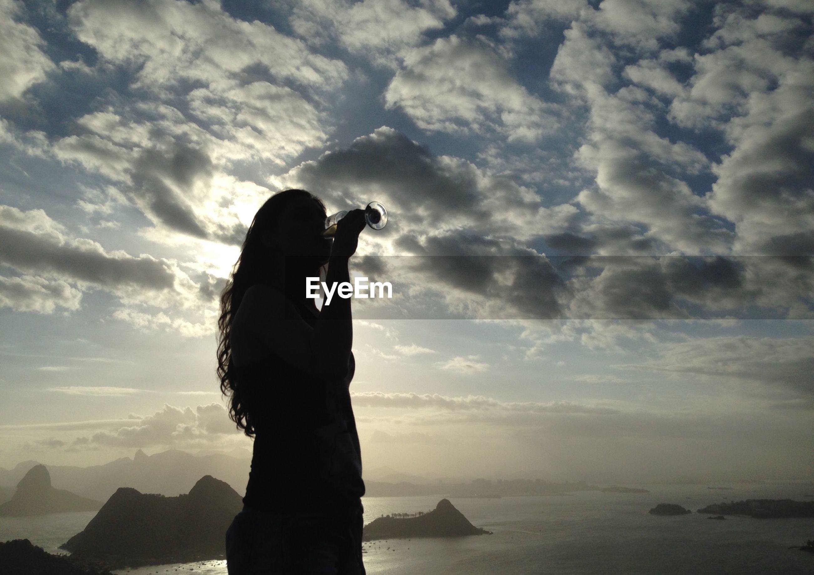 Silhouette woman standing against calm sea