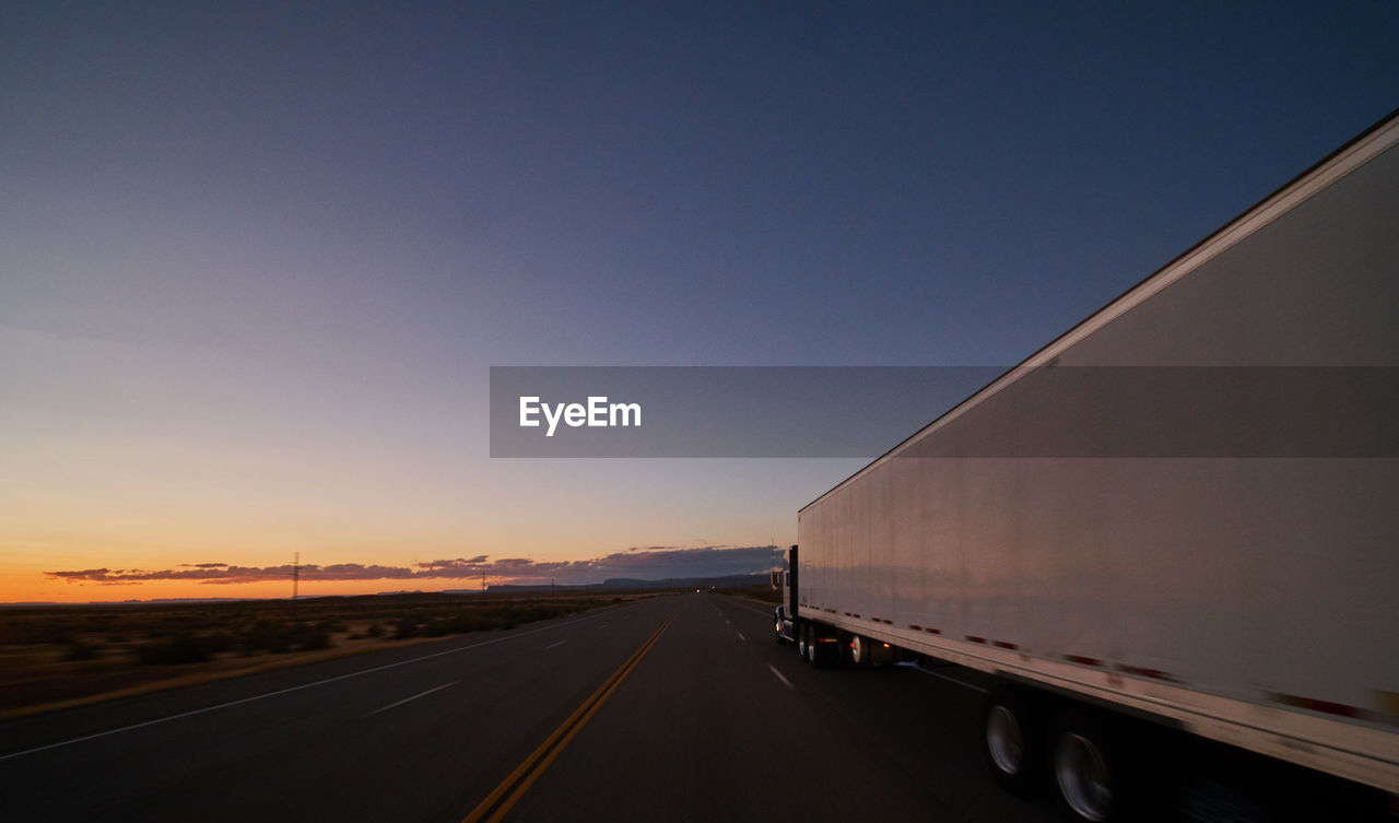 transportation, sky, road, sunset, mode of transportation, direction, land vehicle, copy space, the way forward, nature, no people, diminishing perspective, truck, outdoors, motor vehicle, clear sky, highway, blue, orange color, motion