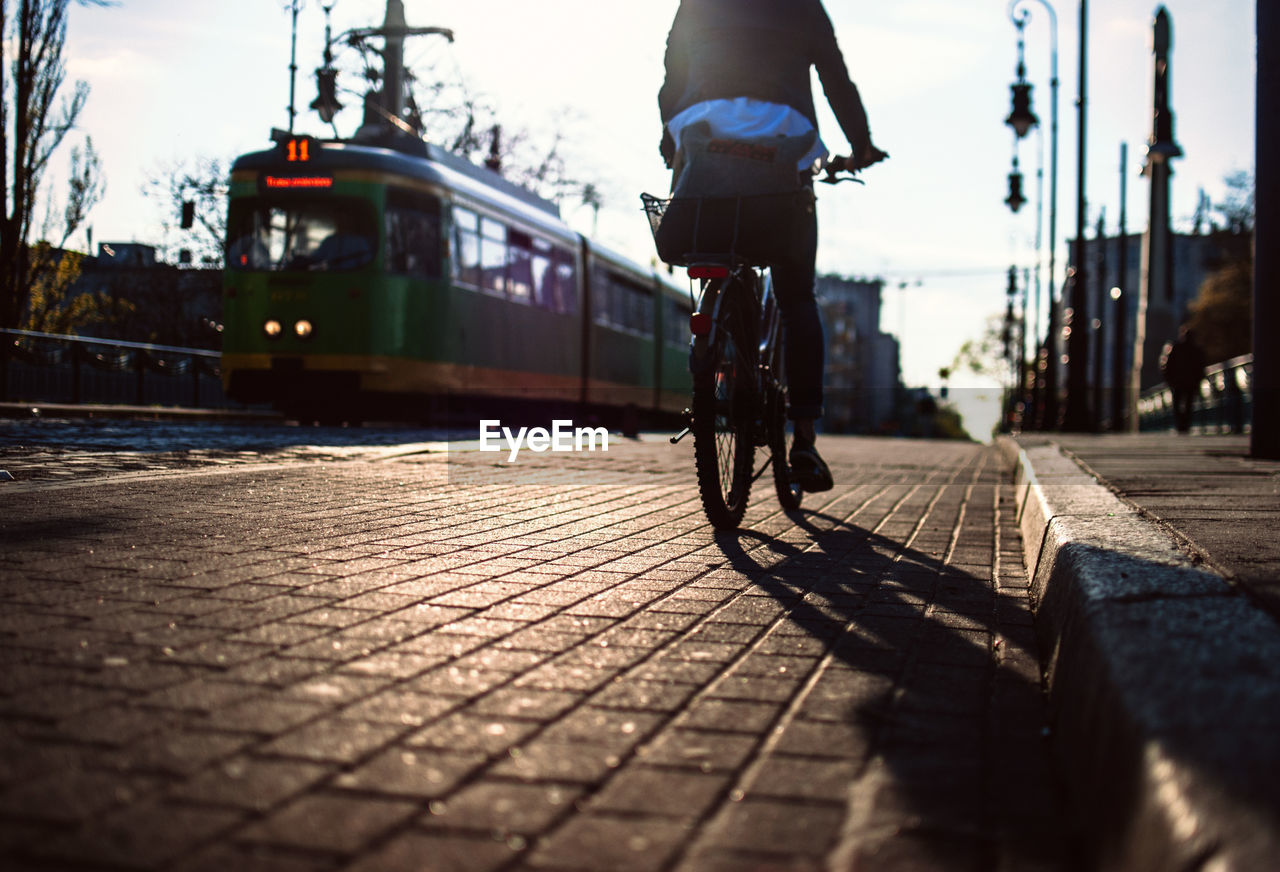 Low Section Of Person Riding Bicycle On Footpath In City