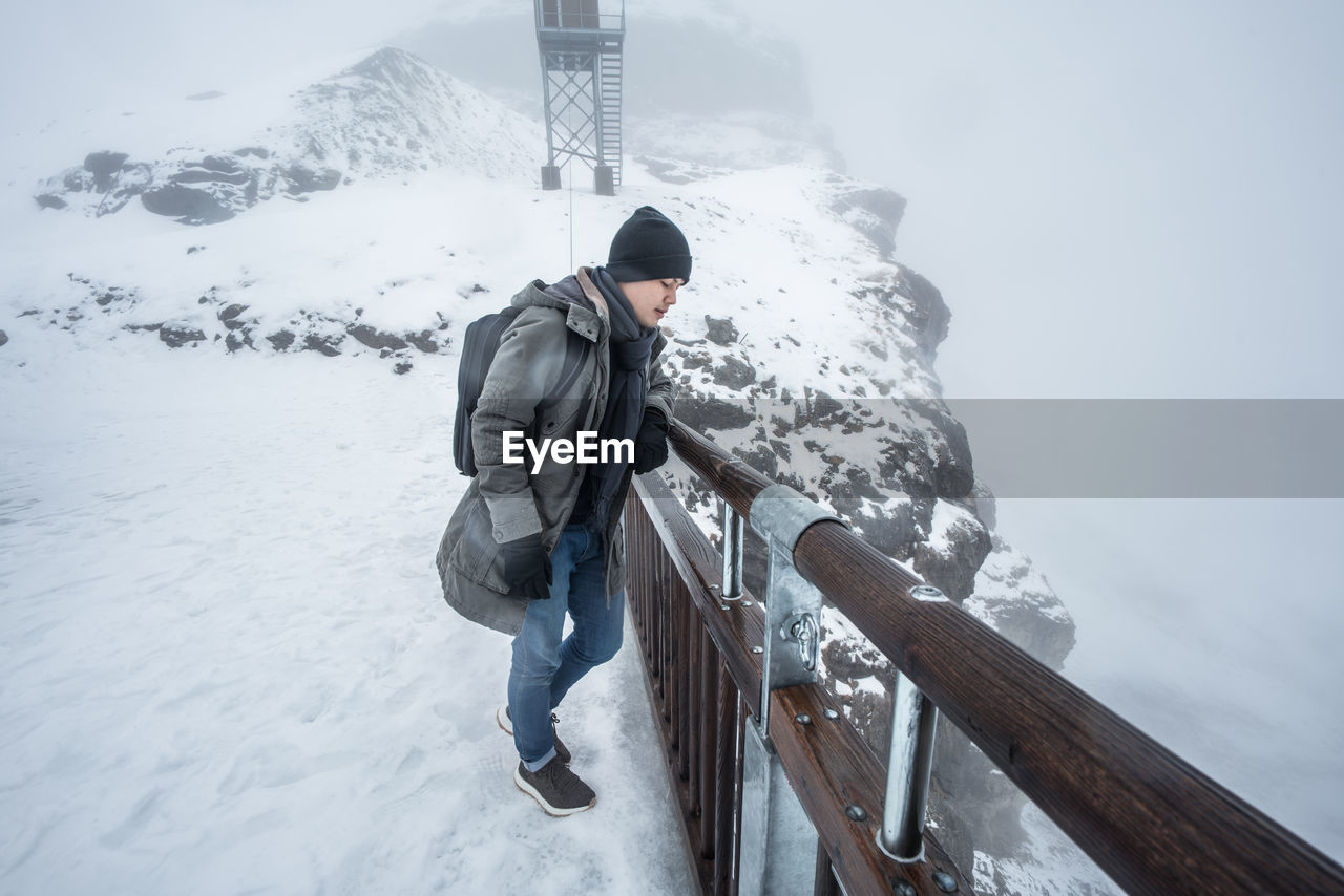 Young Man Standing On Snow Covered Mountain By Railing