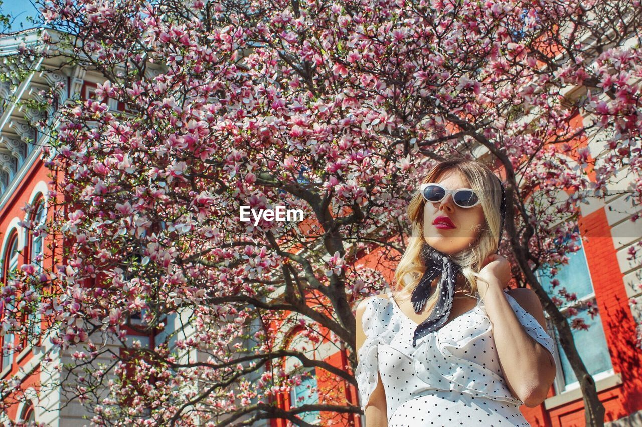 Portrait of young woman wearing sunglasses against tree
