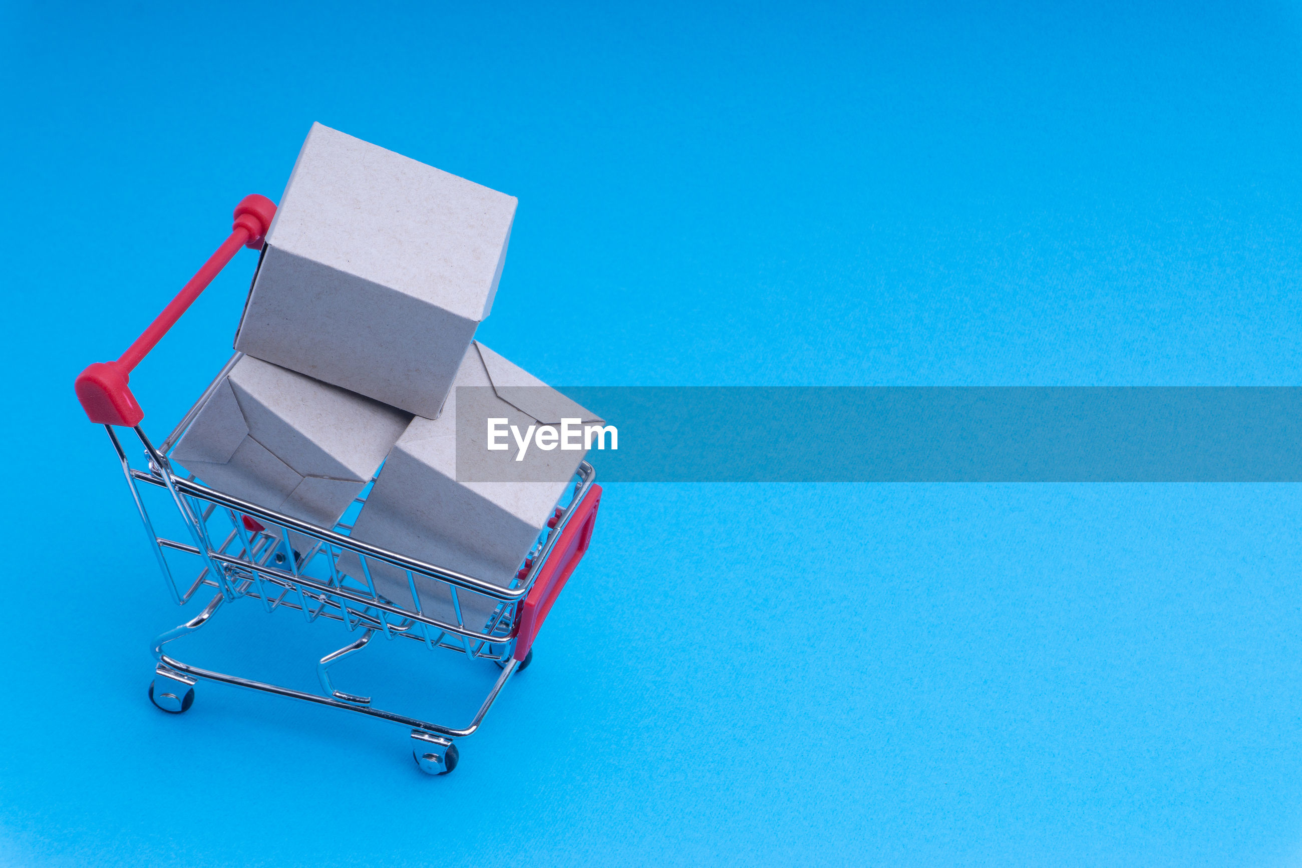 Close-up of miniature shopping cart with cardboard boxes against blue background