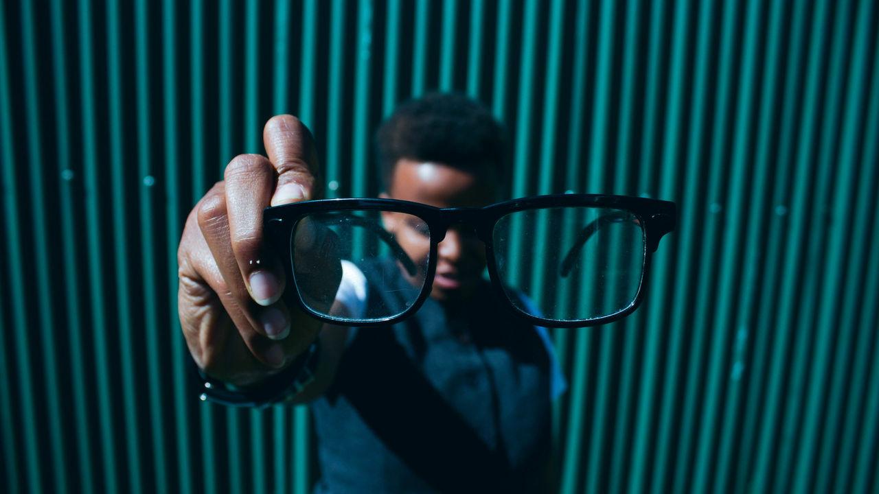 Portrait of person holding eyeglasses