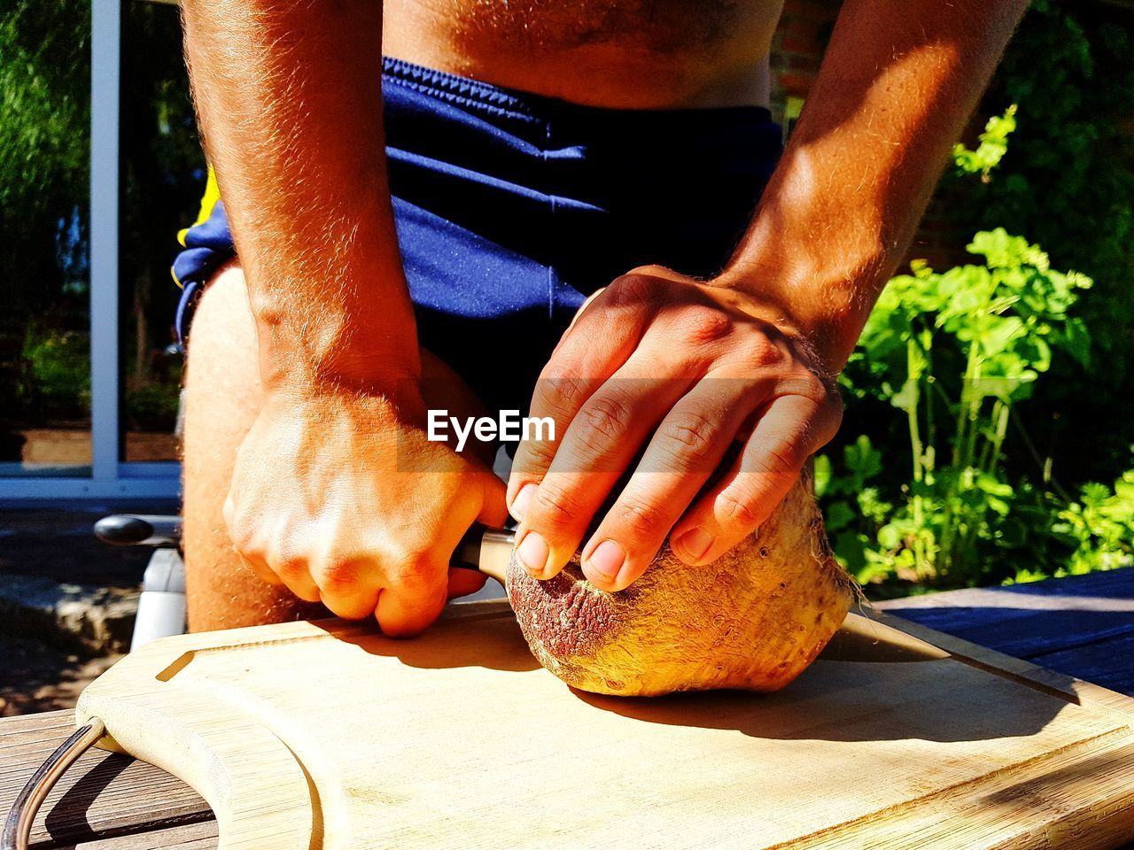 Midsection of men cutting fruit
