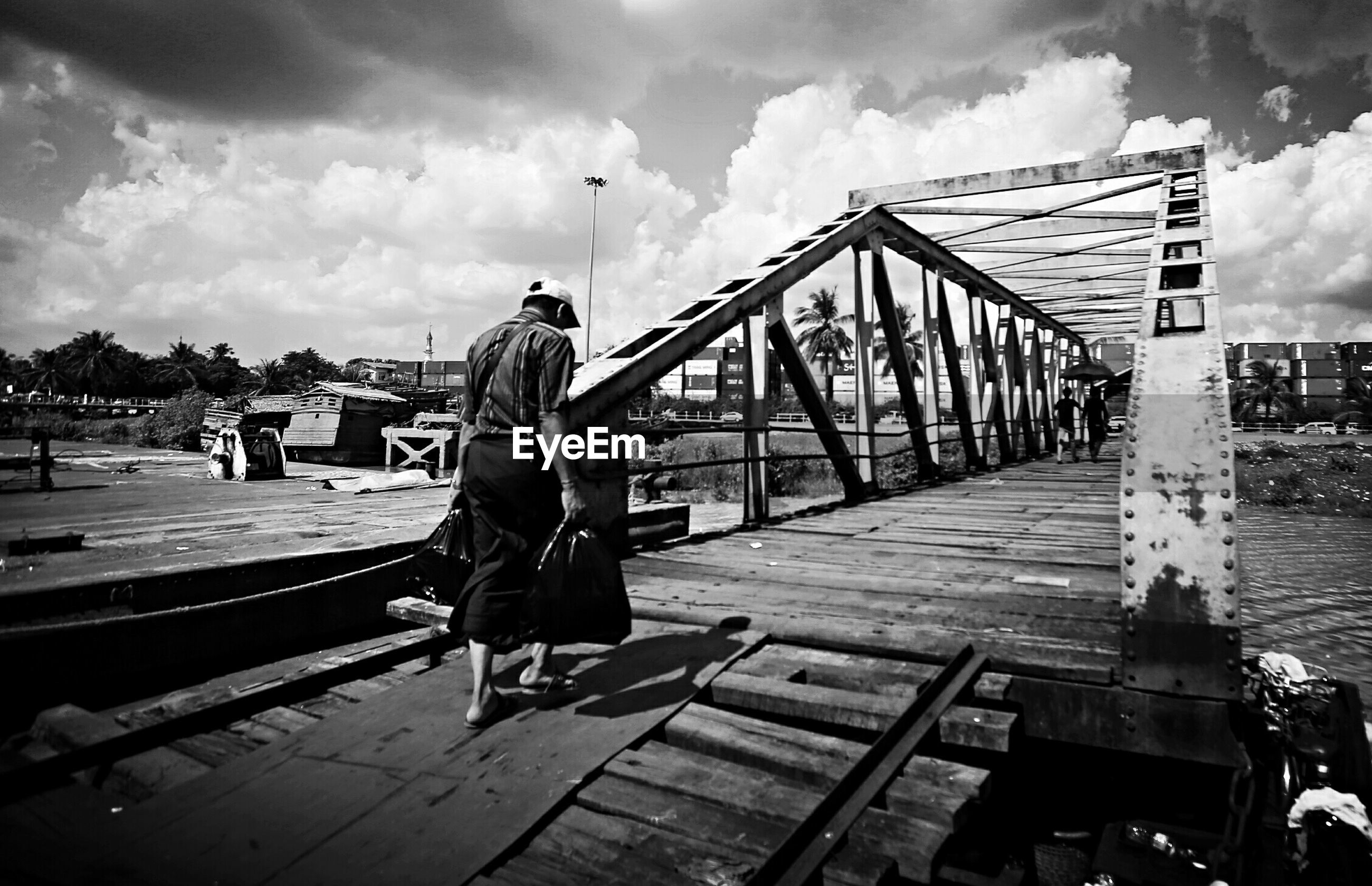 sky, full length, cloud - sky, rear view, railing, lifestyles, men, leisure activity, wood - material, built structure, cloudy, cloud, person, casual clothing, walking, architecture, pier, day