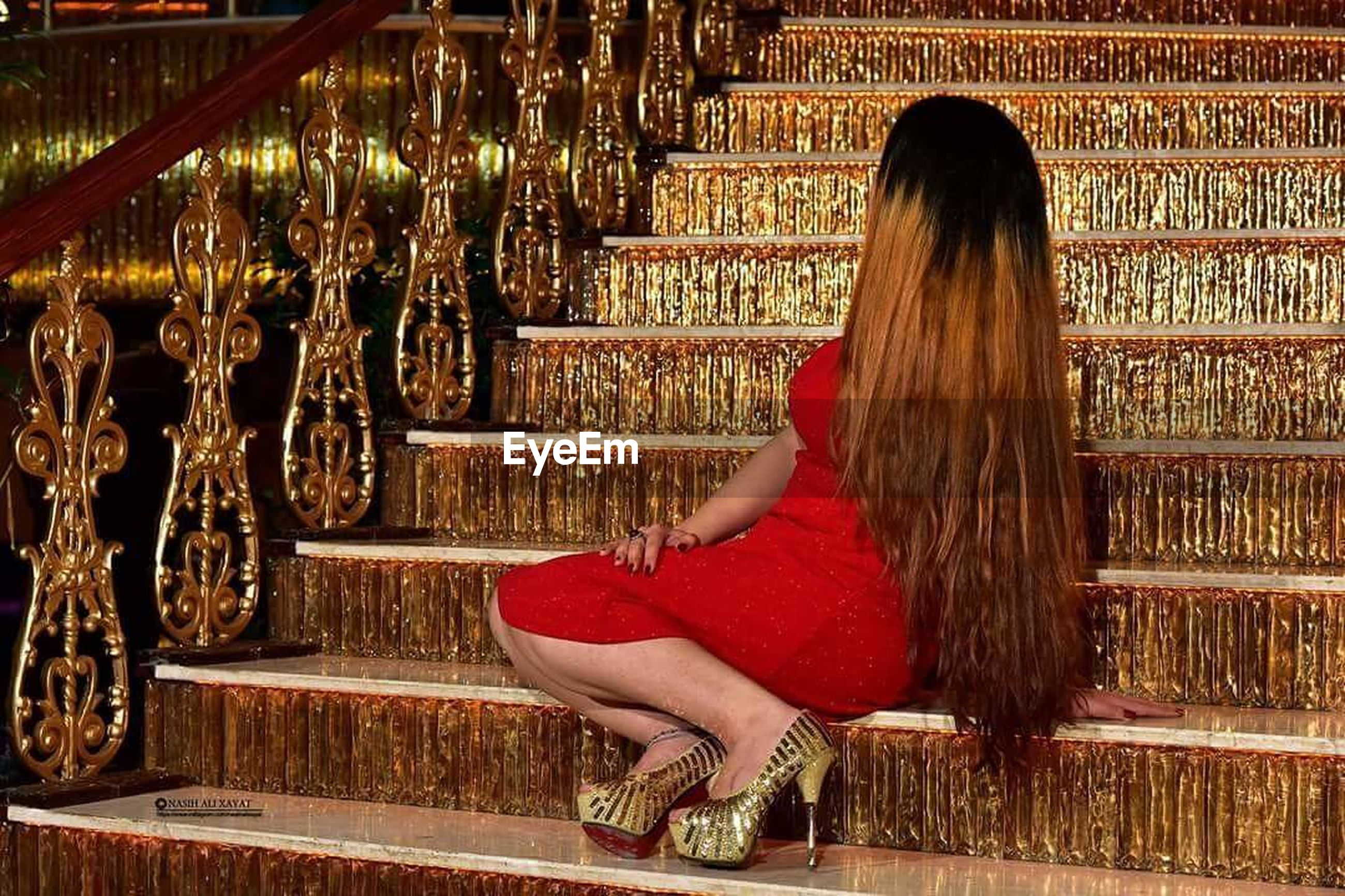 indoors, lifestyles, rear view, leisure activity, person, red, standing, railing, long hair, casual clothing, young women, religion, dress, full length, cultures, built structure, architecture, sitting