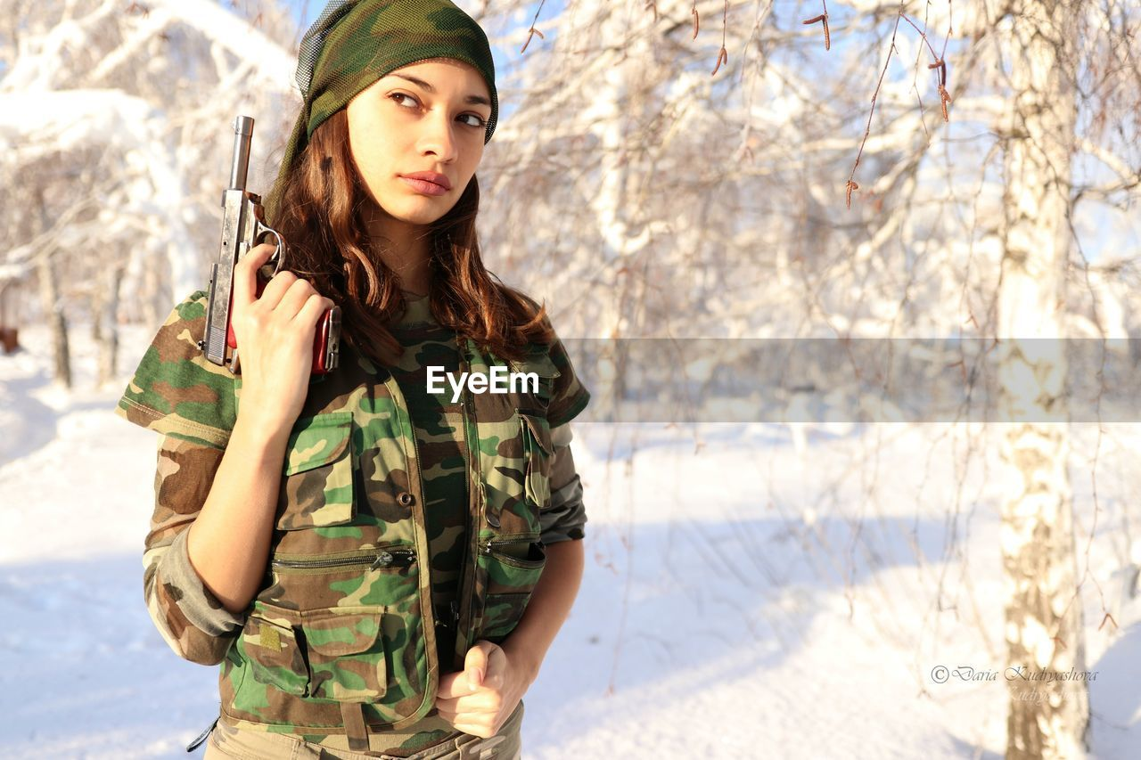 Young female soldier holding gun while standing on snow