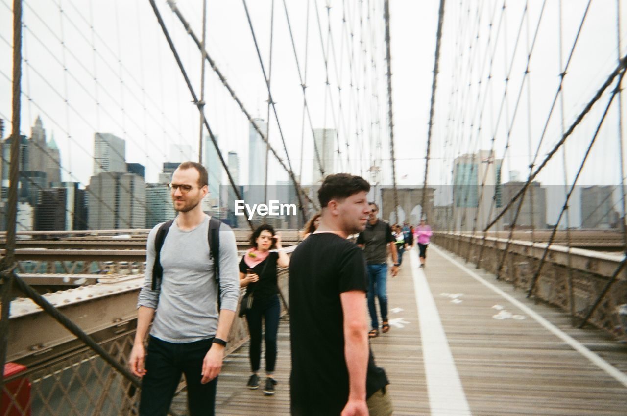 architecture, real people, transportation, young adult, lifestyles, bridge, young men, connection, casual clothing, built structure, men, two people, adult, people, bridge - man made structure, leisure activity, togetherness, day, young women, outdoors, footbridge