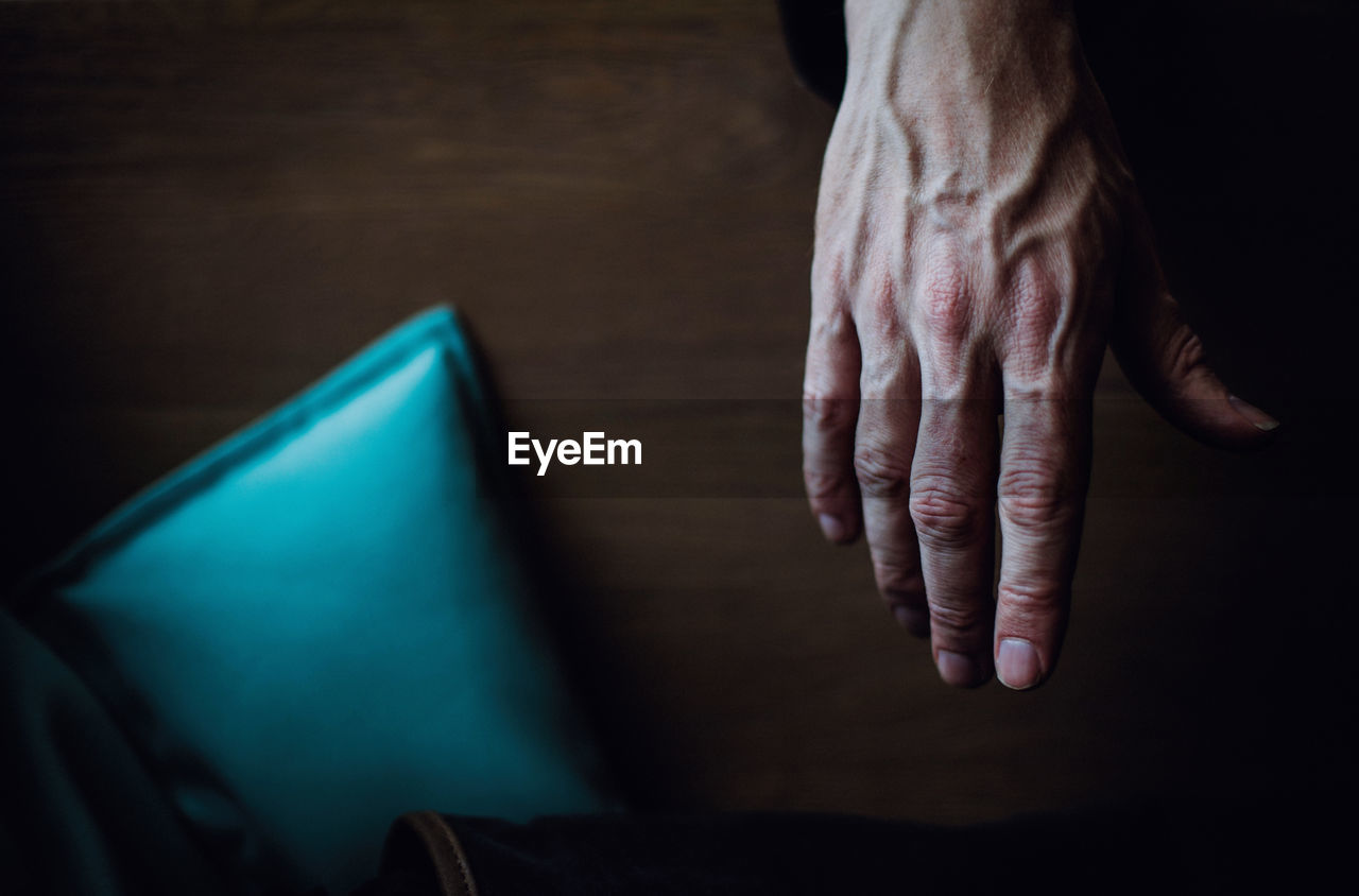 Cropped Hand Of Man Over Wooden Table