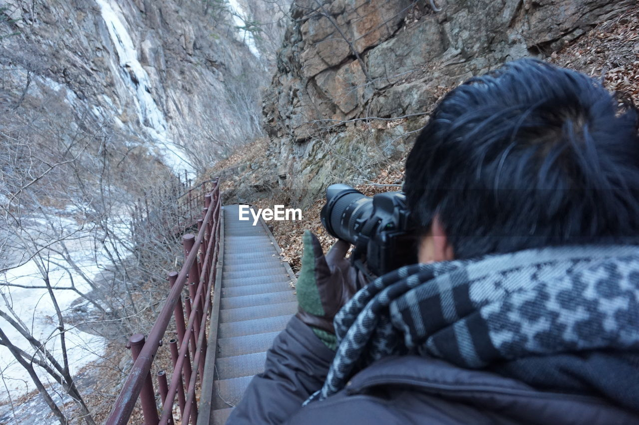 Man Photographing Steps Amidst Mountains During Winter