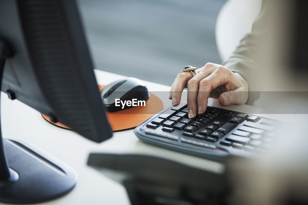 hand, human hand, computer, technology, selective focus, connection, one person, table, communication, computer equipment, real people, keyboard, desk, human body part, wireless technology, office, business, computer keyboard, furniture, surfing the net