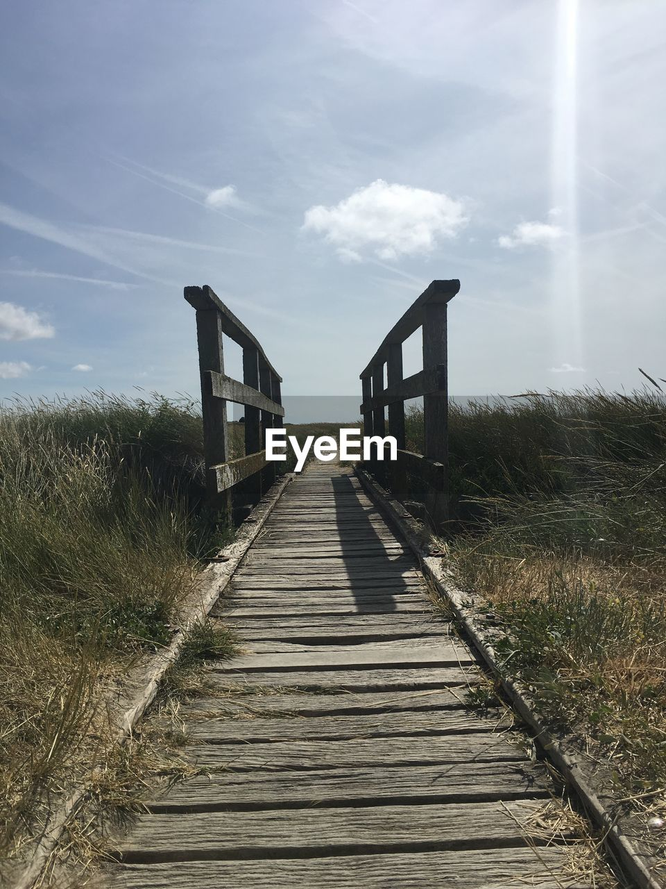 Boardwalk Leading Towards Built Structure Against Sky
