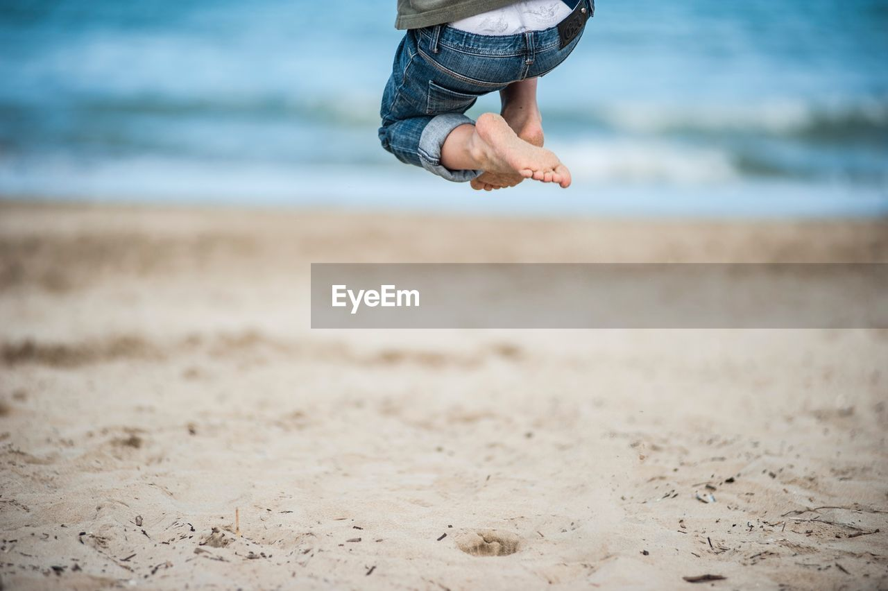 Low Section Of Boy Jumping On Sand At Beach