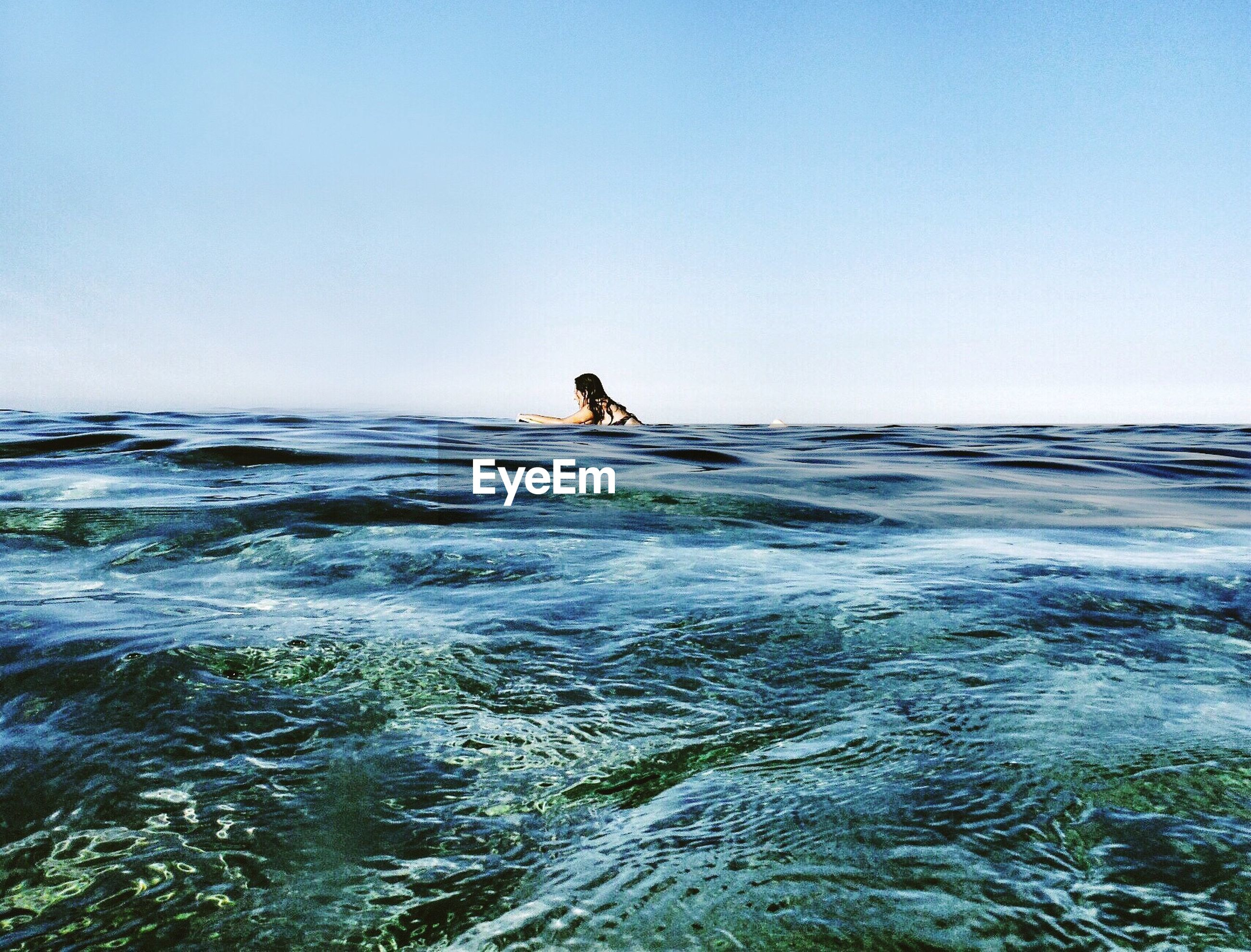 Mid distance view of woman swimming in sea against sky