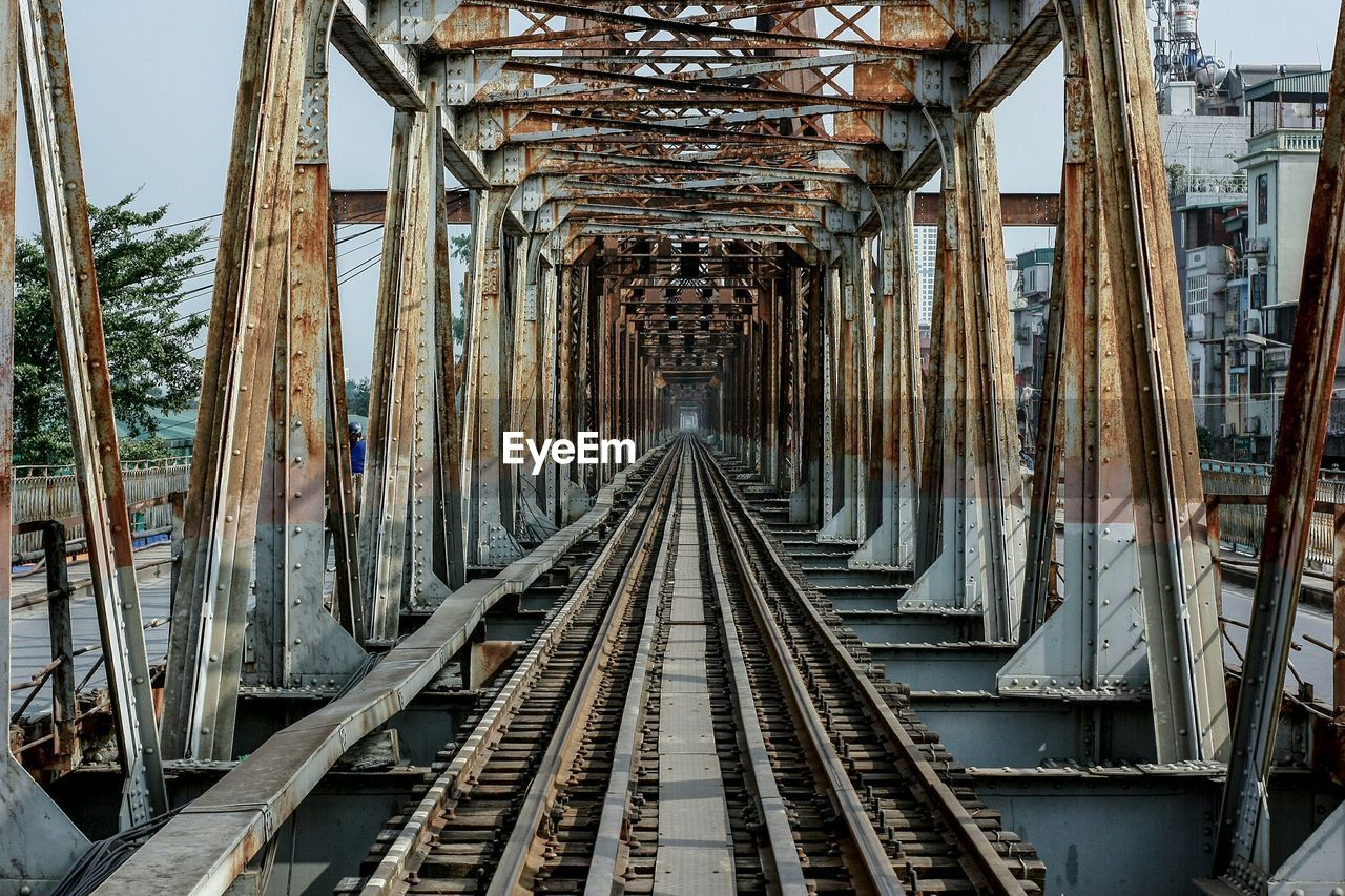 diminishing perspective, direction, the way forward, rail transportation, architecture, railroad track, track, vanishing point, transportation, built structure, no people, day, metal, connection, rusty, bridge, outdoors, railway bridge, mode of transportation, bridge - man made structure, long, parallel