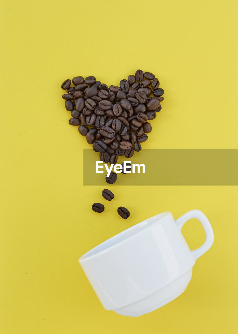 High angle view of heart shape roasted coffee beans and cup against yellow background