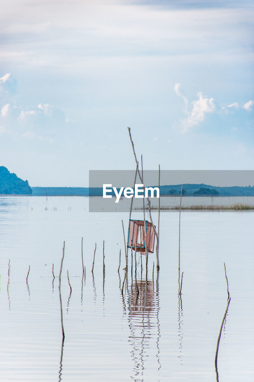 water, sky, cloud - sky, tranquil scene, beauty in nature, tranquility, day, nature, waterfront, scenics - nature, reflection, no people, non-urban scene, sea, nautical vessel, wood - material, outdoors, bird, wooden post