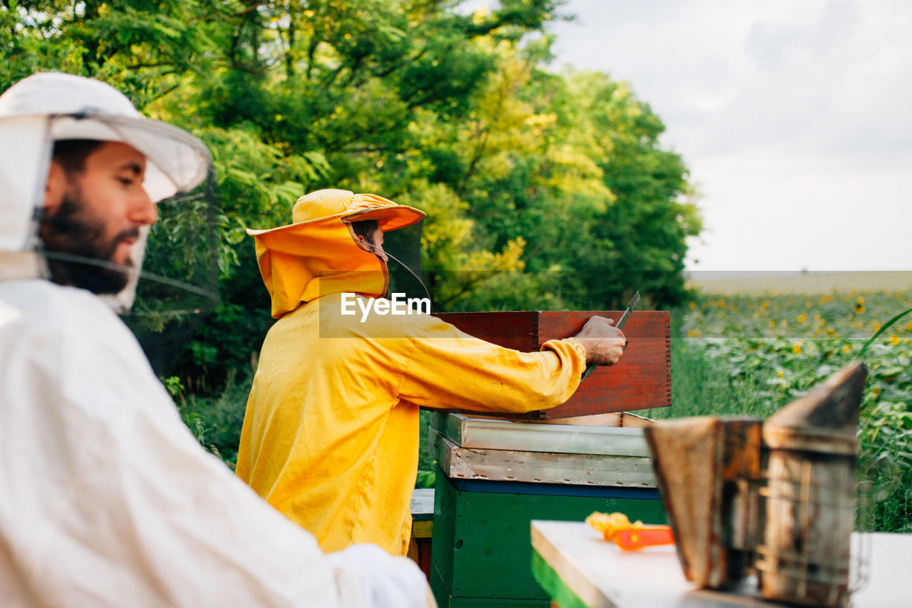 Beekeepers Standing By Containers On Field