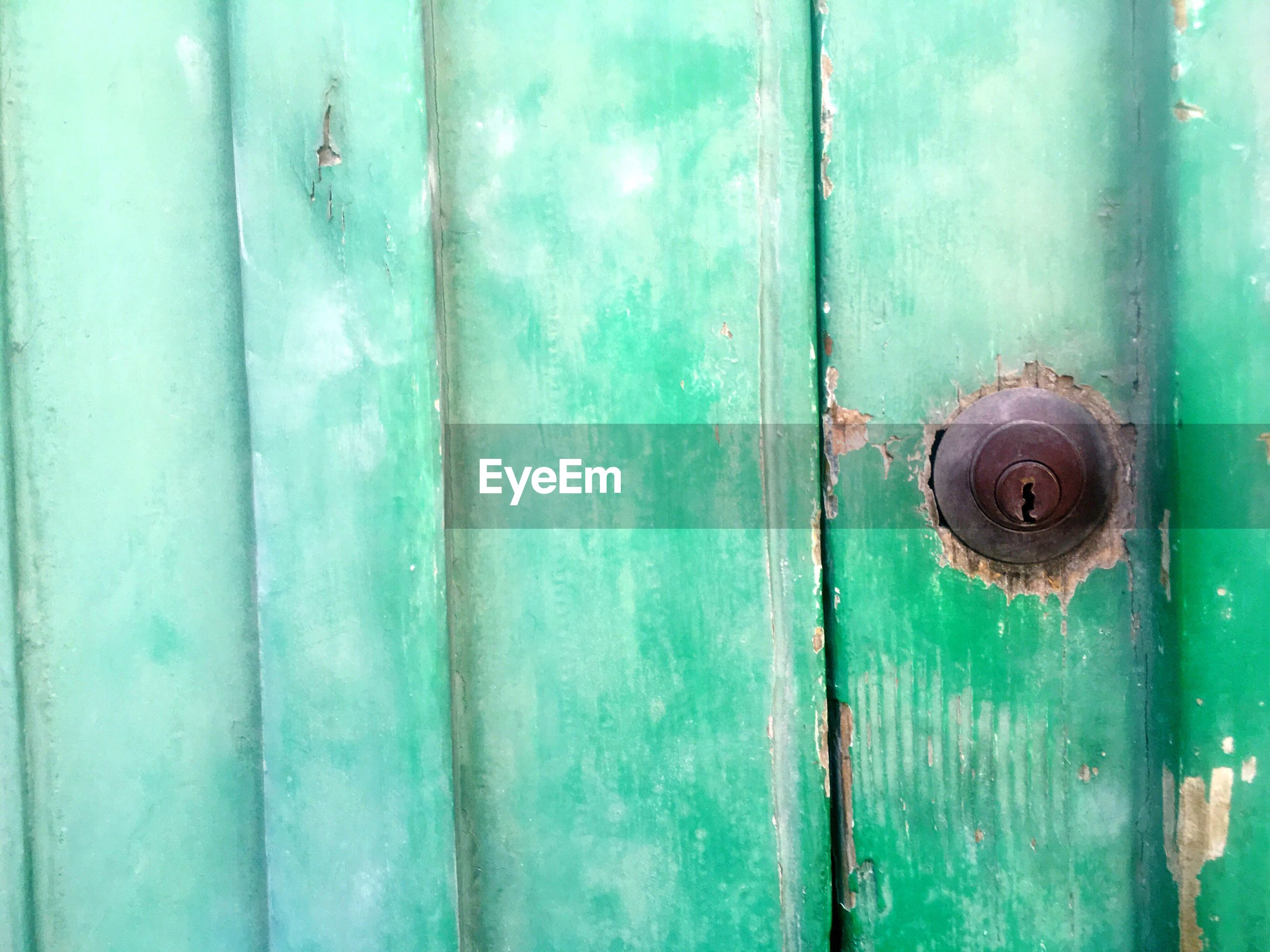 High angle view of rusty keyhole amidst green wooden door