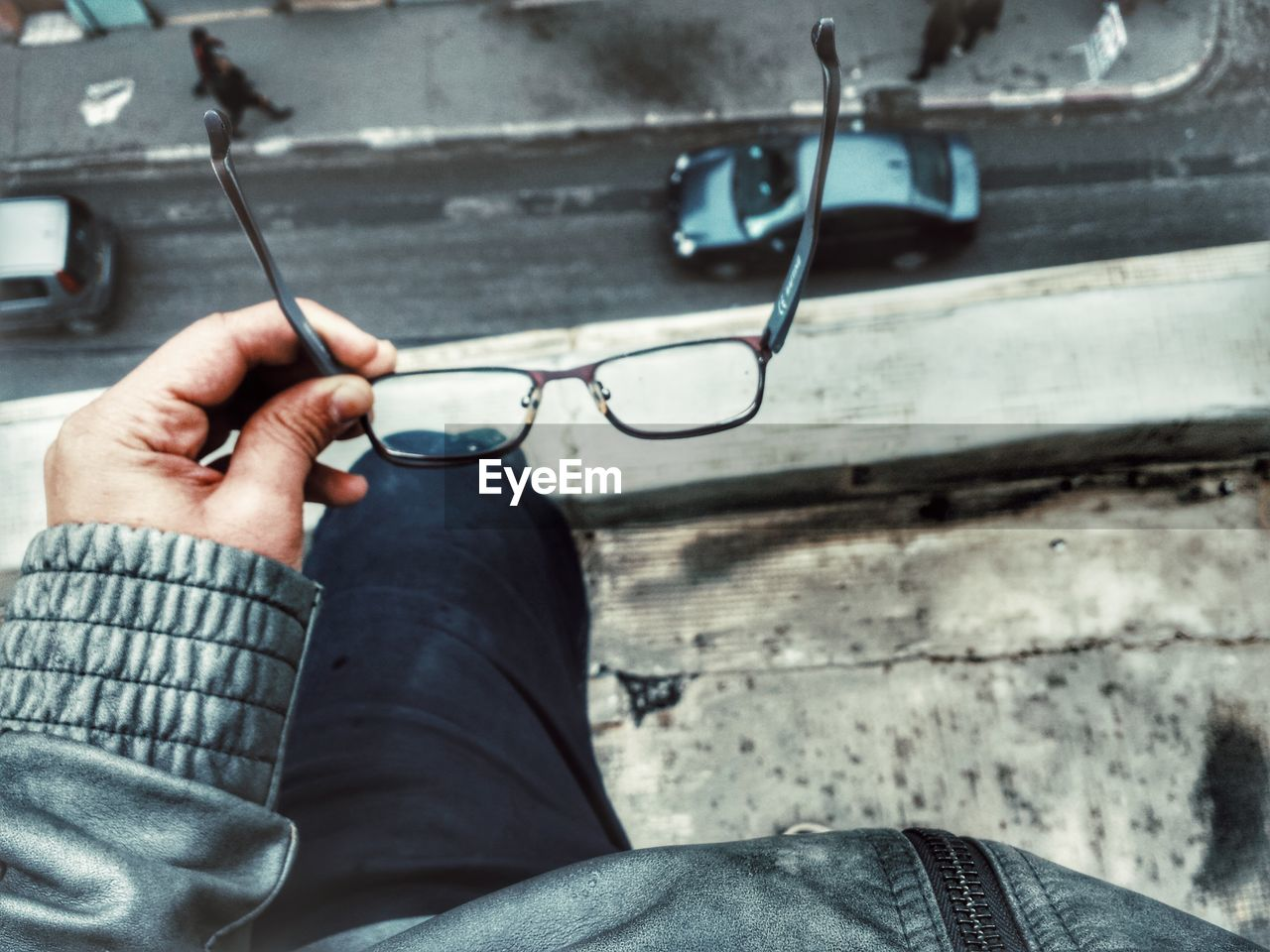 Cropped image of person holding eyeglasses while standing on building terrace
