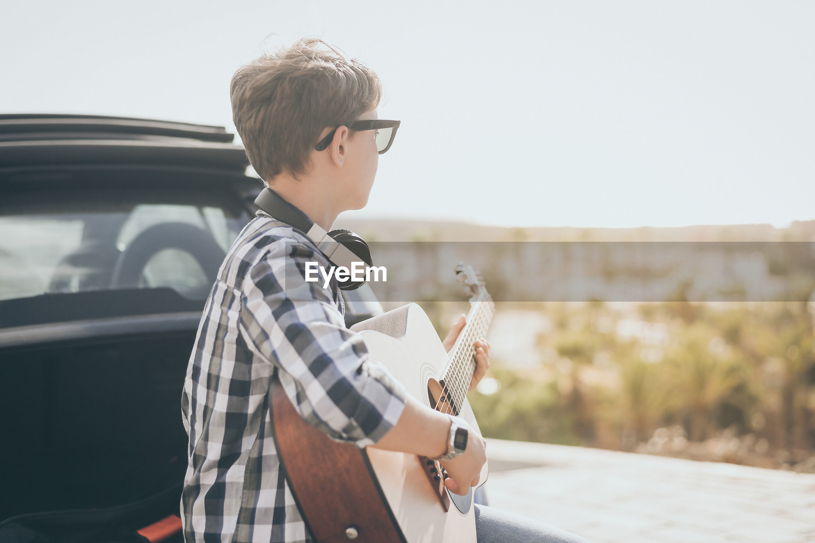 Young boy playing guitar and using smartphone outdoor. teen enjoying music