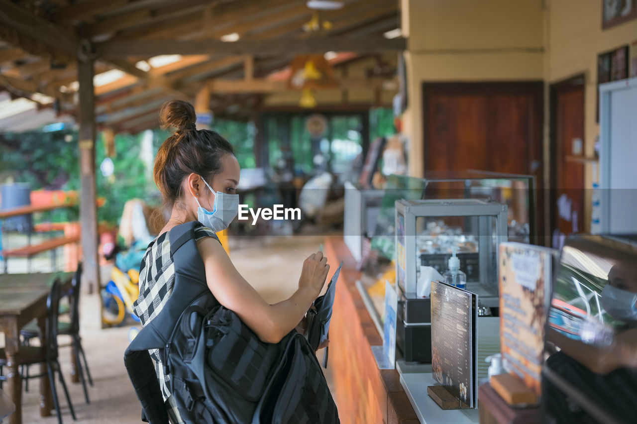 Side view point of young women wearing surgical mask with backpack buying coffee at coffee shop