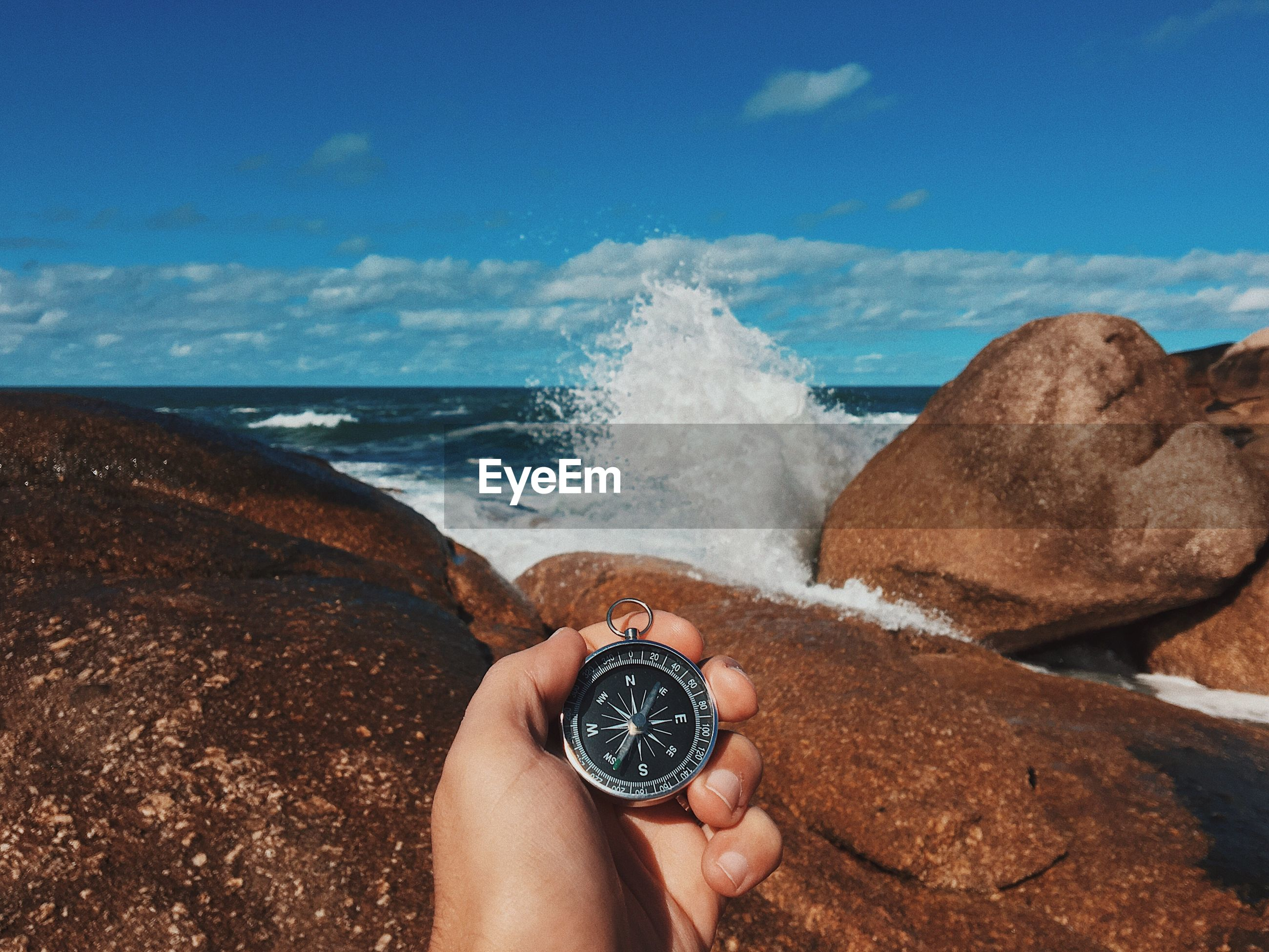 Cropped image of person holding navigational compass against rocky shore