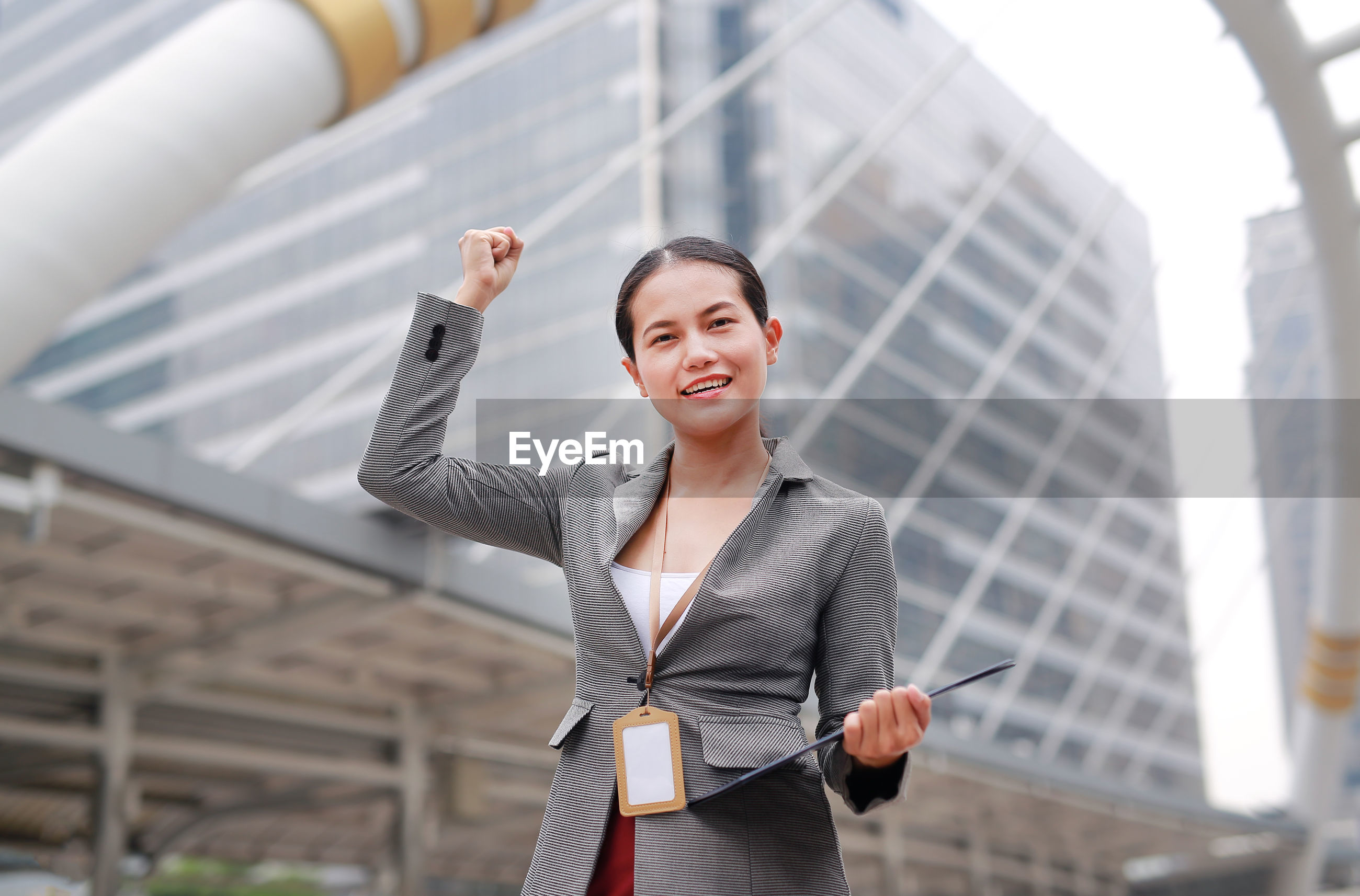 Happy businesswoman clenching fist against office building