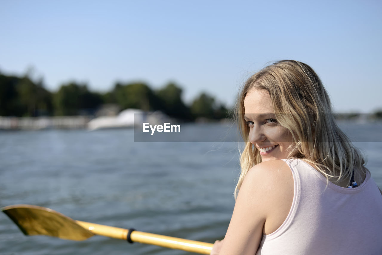 Rear View Portrait Of Young Woman Smiling While Sailing Boat In Lake