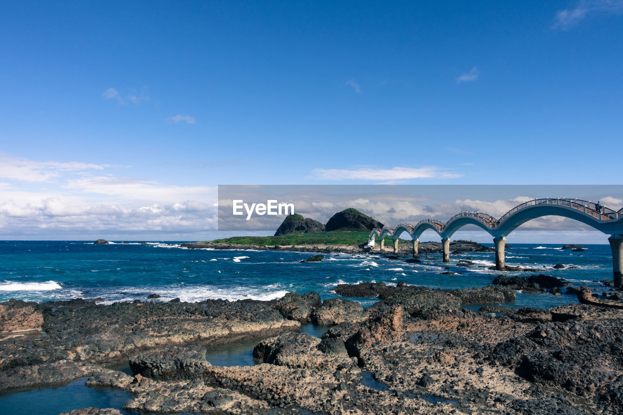 sea, sky, bridge - man made structure, water, nature, arch, beauty in nature, built structure, day, architecture, beach, outdoors, scenics, no people, blue, horizon over water