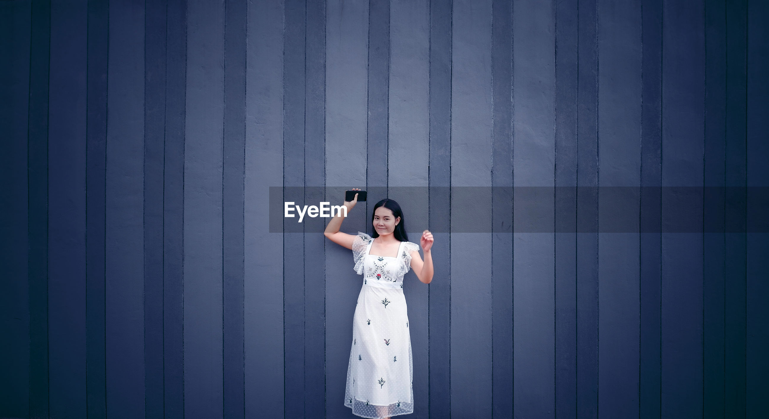 Portrait of woman holding mobile phone standing against wall