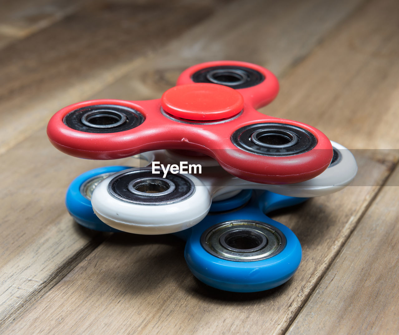High Angle View Of Colorful Fidget Spinners On Wooden Table