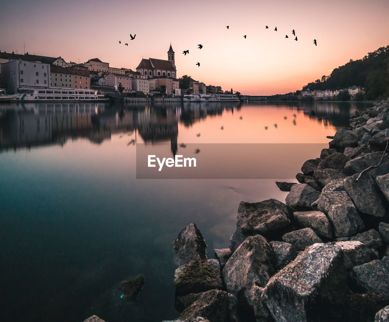 water, sky, sunset, reflection, built structure, building exterior, vertebrate, rock, nature, architecture, bird, animal themes, animal, rock - object, beauty in nature, solid, waterfront, flying, group of animals, no people, outdoors, flock of birds