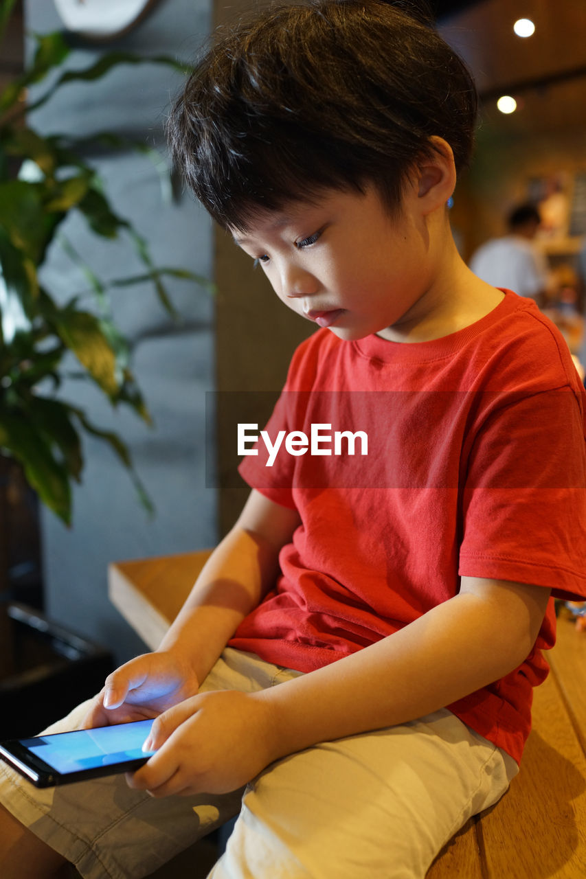 Boy Using Smart Phone At Home