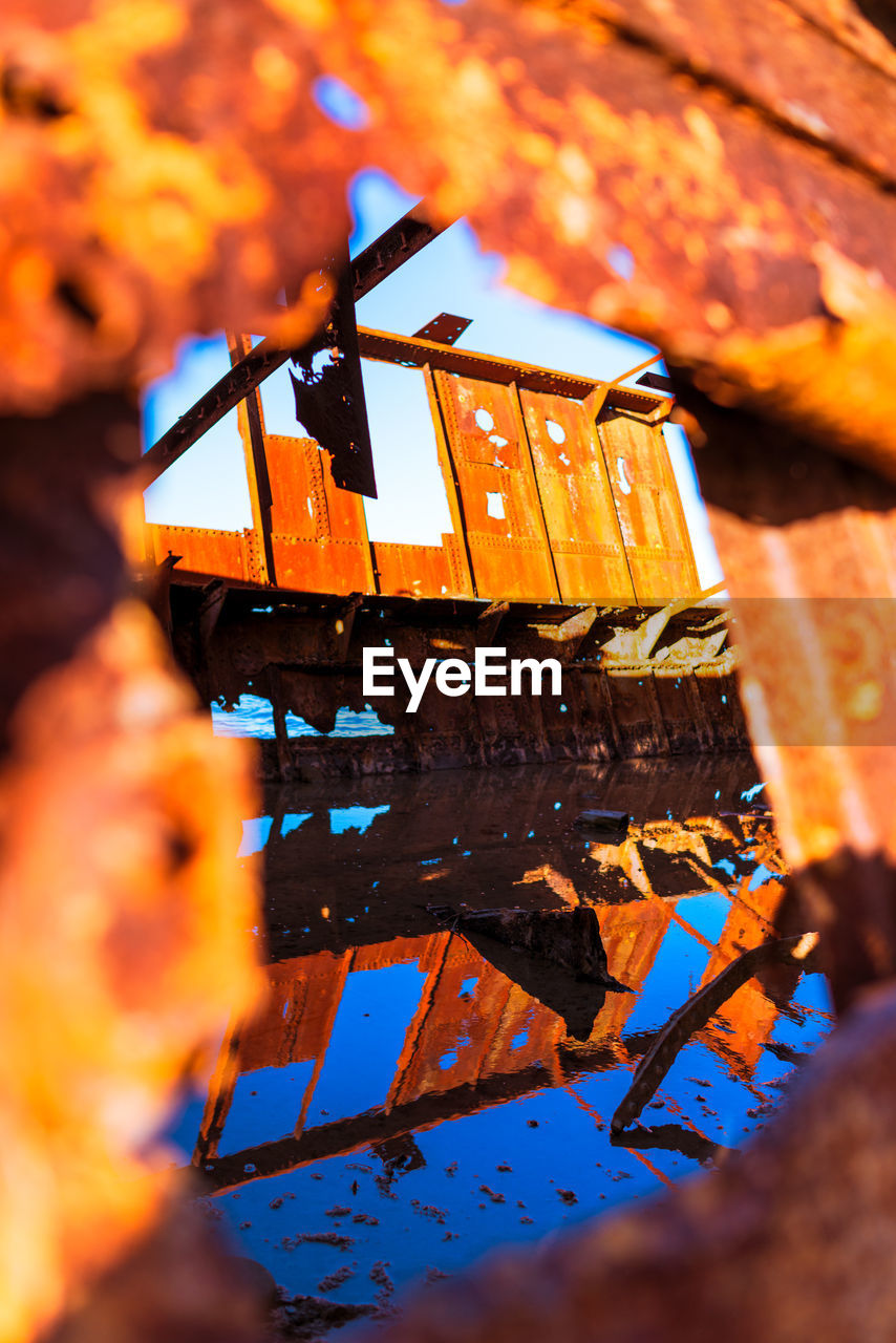 selective focus, close-up, no people, orange color, nature, metal, outdoors, focus on background, heat - temperature, fire, high angle view, technology, fire - natural phenomenon, day, flame, industry, food, water