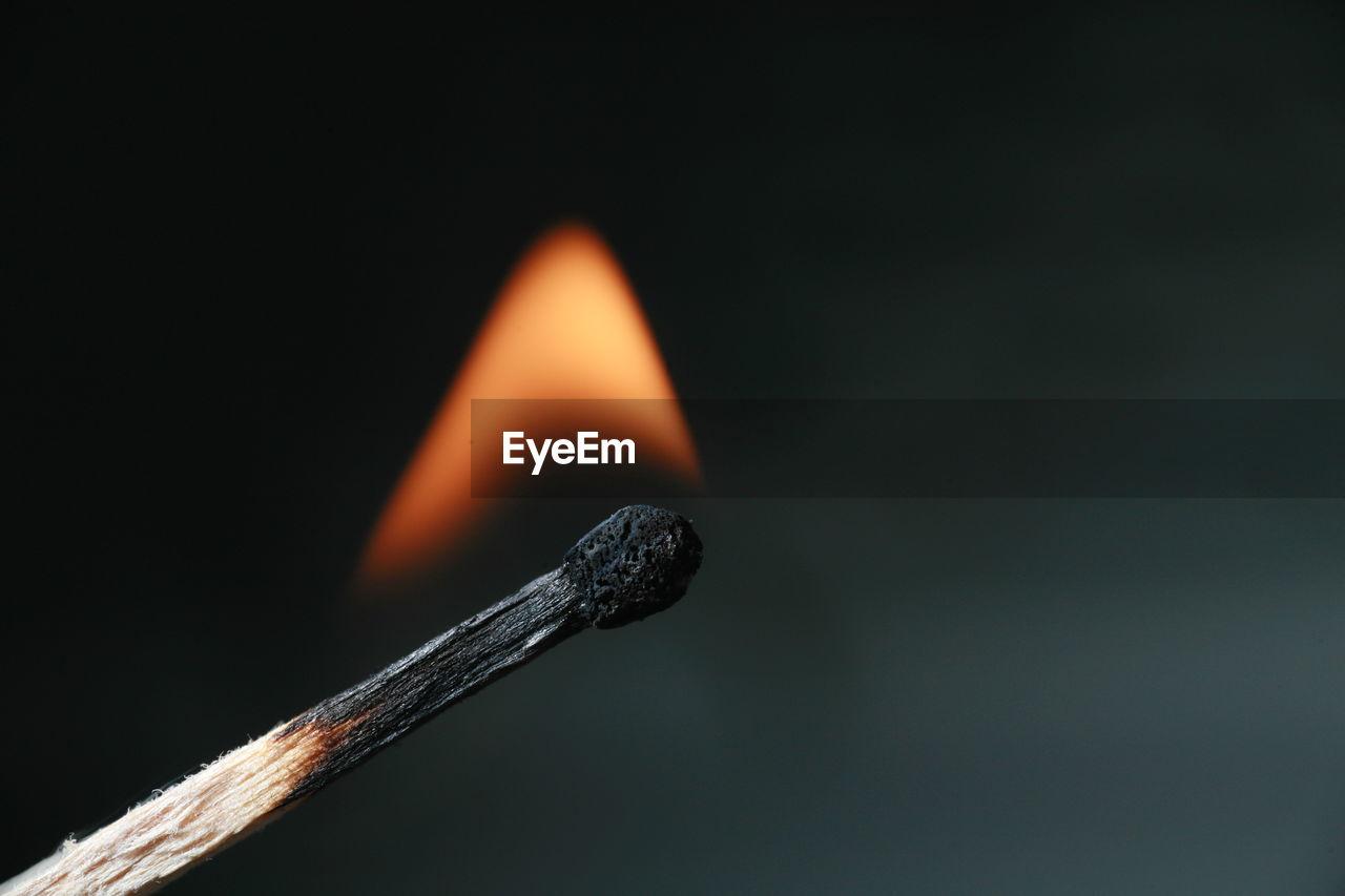 Close-up of burning match on black background