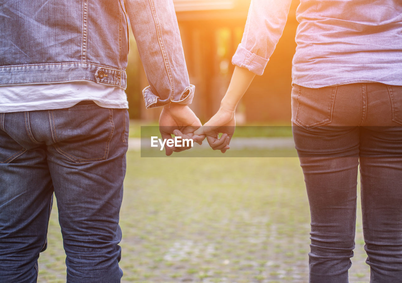 love, positive emotion, togetherness, bonding, emotion, holding hands, midsection, two people, men, romance, women, adult, couple - relationship, real people, lifestyles, focus on foreground, people, casual clothing, heterosexual couple, day, hand, outdoors, care, finger