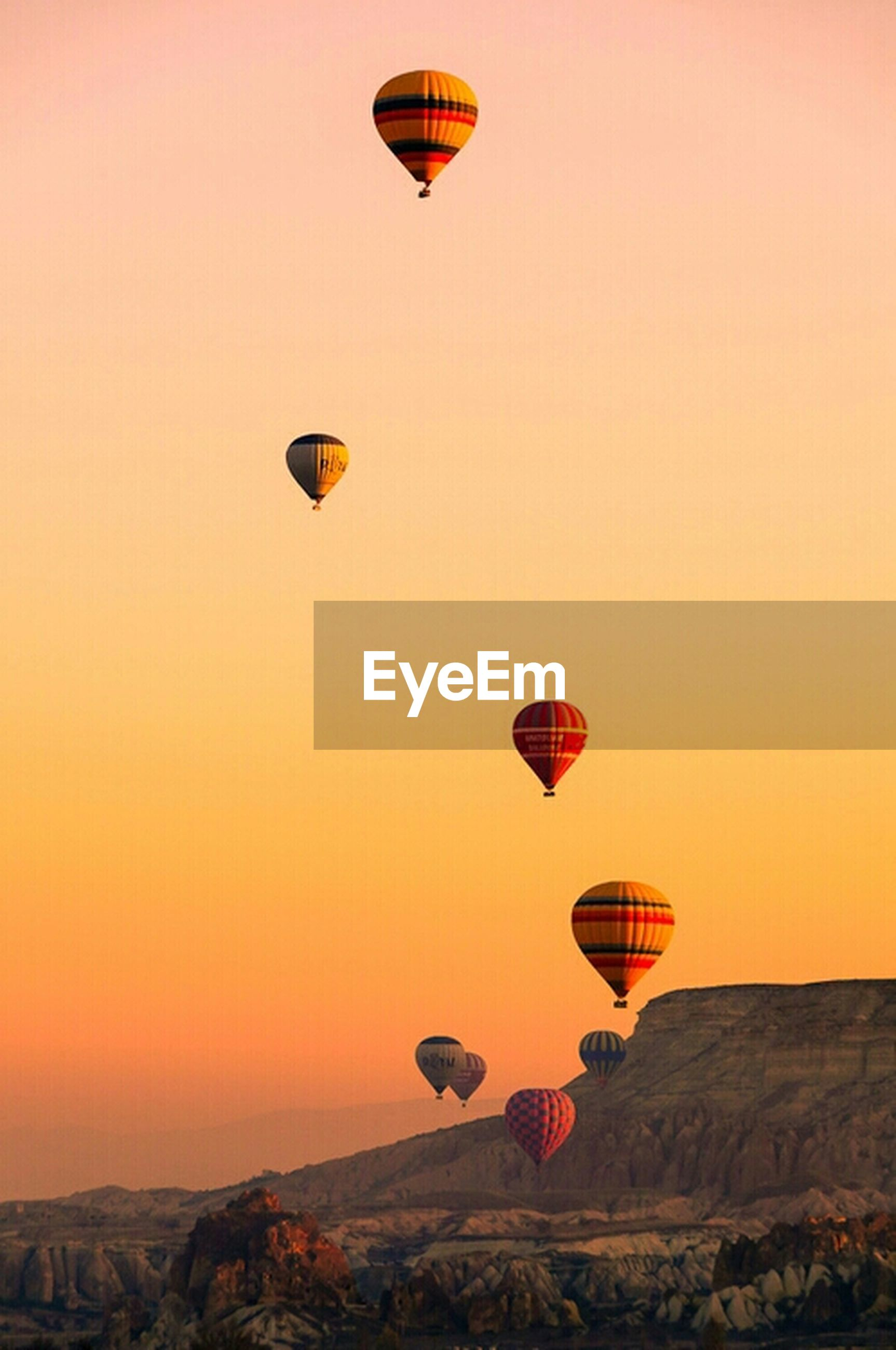 clear sky, sunset, copy space, orange color, hot air balloon, transportation, red, mid-air, low angle view, guidance, flying, parachute, yellow, adventure, scenics, lighting equipment, sky, outdoors, tranquility, communication