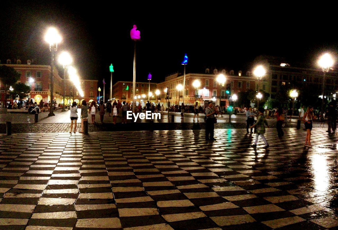 large group of people, night, illuminated, real people, built structure, leisure activity, lifestyles, architecture, men, outdoors, building exterior, sky, people