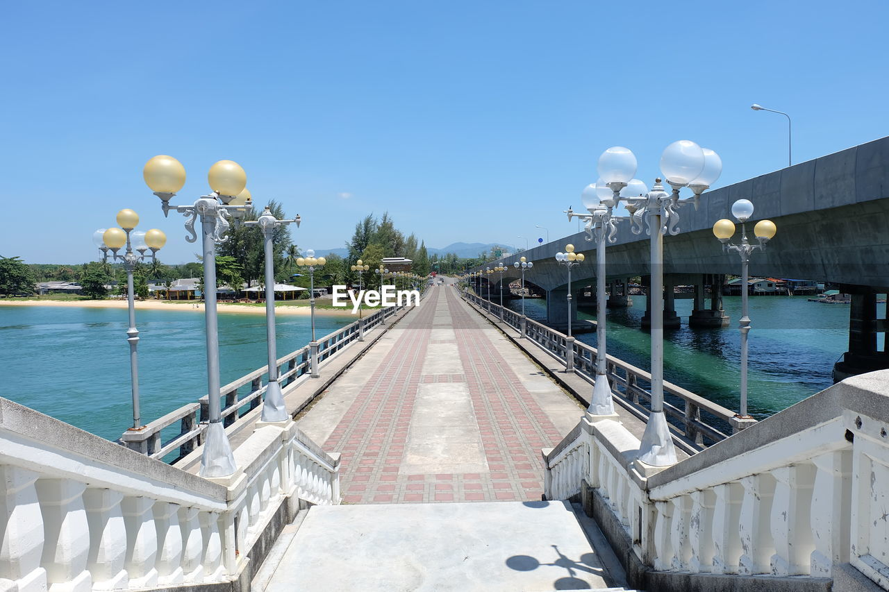 water, architecture, sky, built structure, railing, nature, diminishing perspective, lighting equipment, clear sky, the way forward, day, no people, street light, direction, building exterior, bridge, outdoors, pool, vanishing point, swimming pool