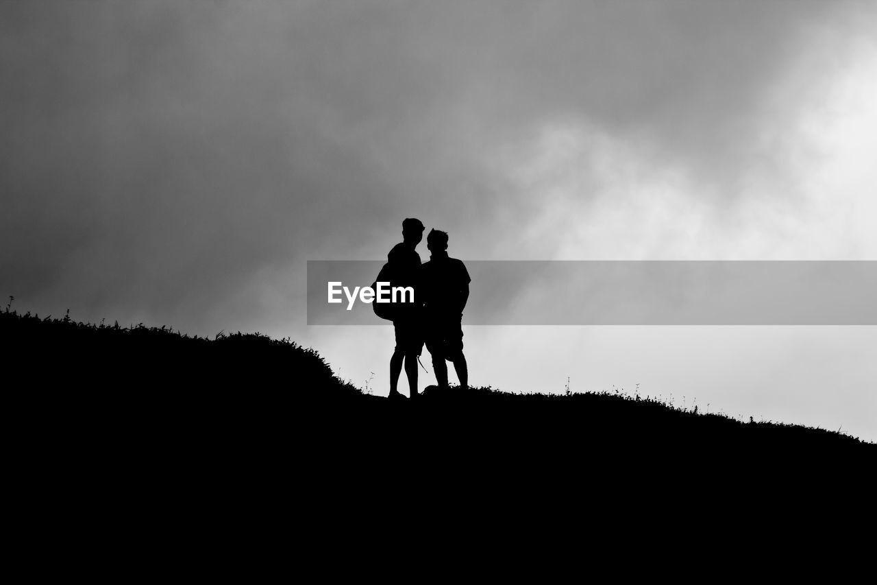 Silhouette Of Two Men On The Top Of A Hill