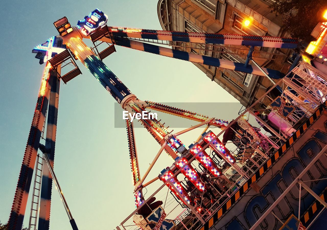 amusement park, low angle view, arts culture and entertainment, built structure, clear sky, no people, architecture, amusement park ride, outdoors, day, illuminated, sky