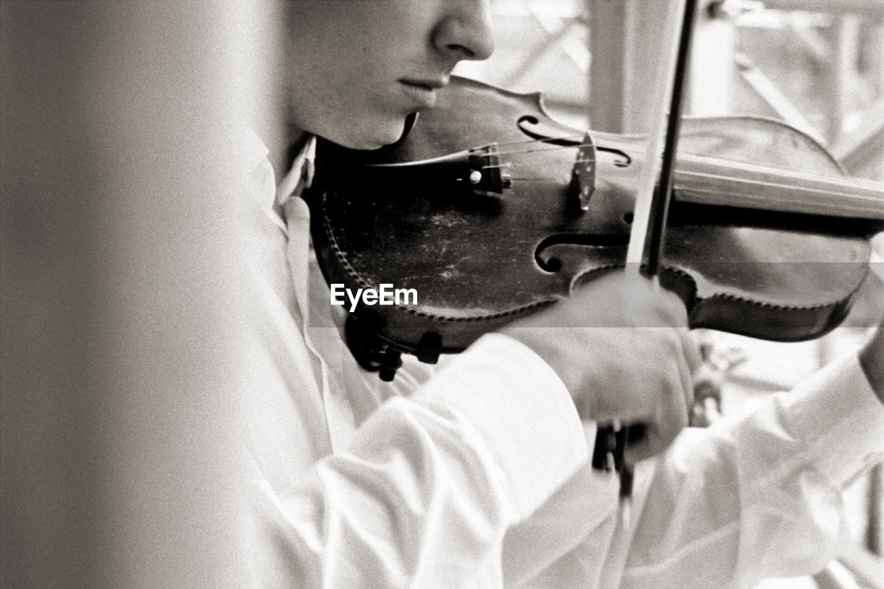 Midsection of man playing violin