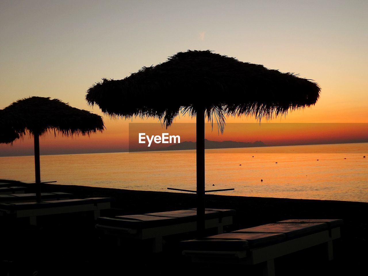 sunset, sea, beauty in nature, beach, tranquility, water, tranquil scene, nature, scenics, silhouette, no people, outdoors, idyllic, thatched roof, horizon over water, tree, sky, clear sky, palm tree, day