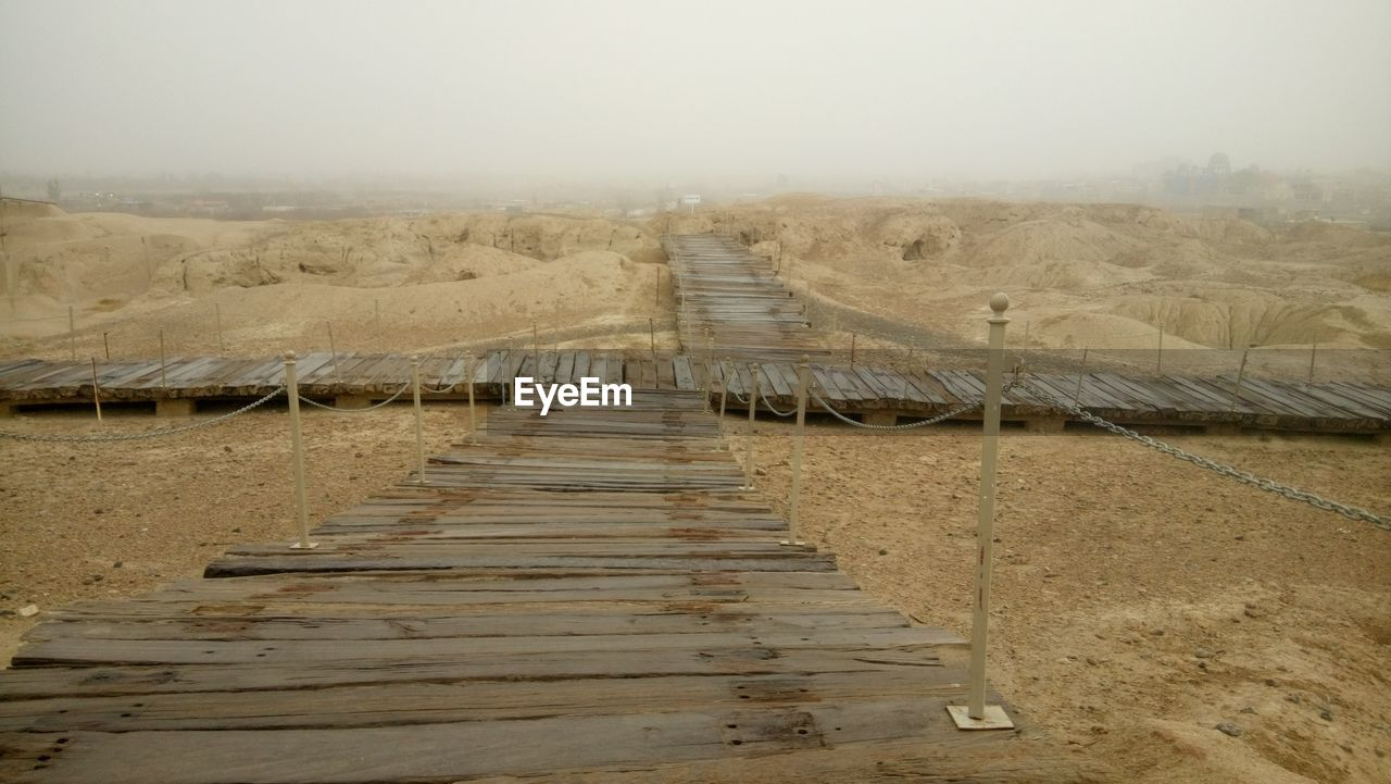 landscape, environment, sky, the way forward, direction, no people, nature, tranquil scene, land, tranquility, day, scenics - nature, fog, built structure, outdoors, non-urban scene, desert, architecture, wood - material, climate, arid climate