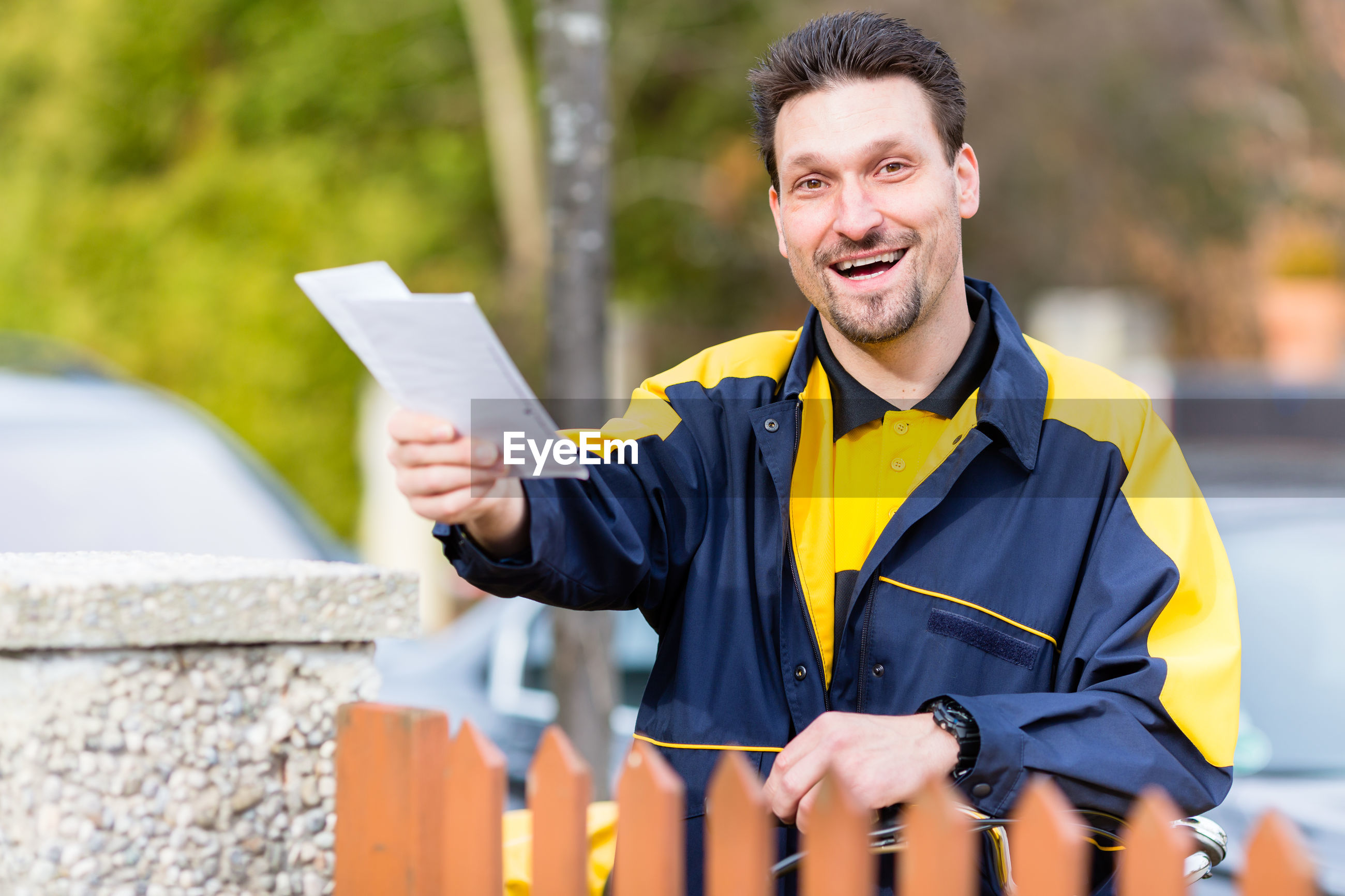 Portrait of smiling postal worker holding yellow while standing outdoors