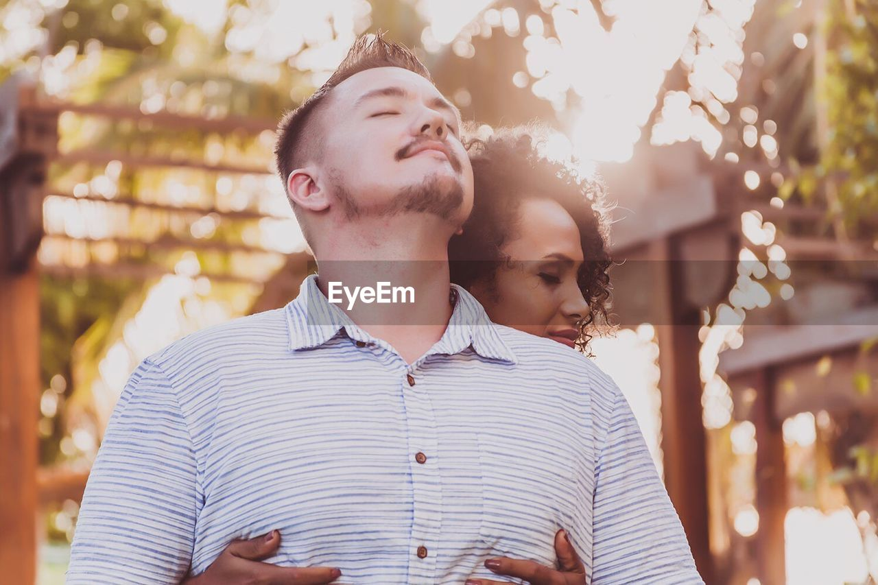 Low Angle View Of Woman Embracing Man At Park