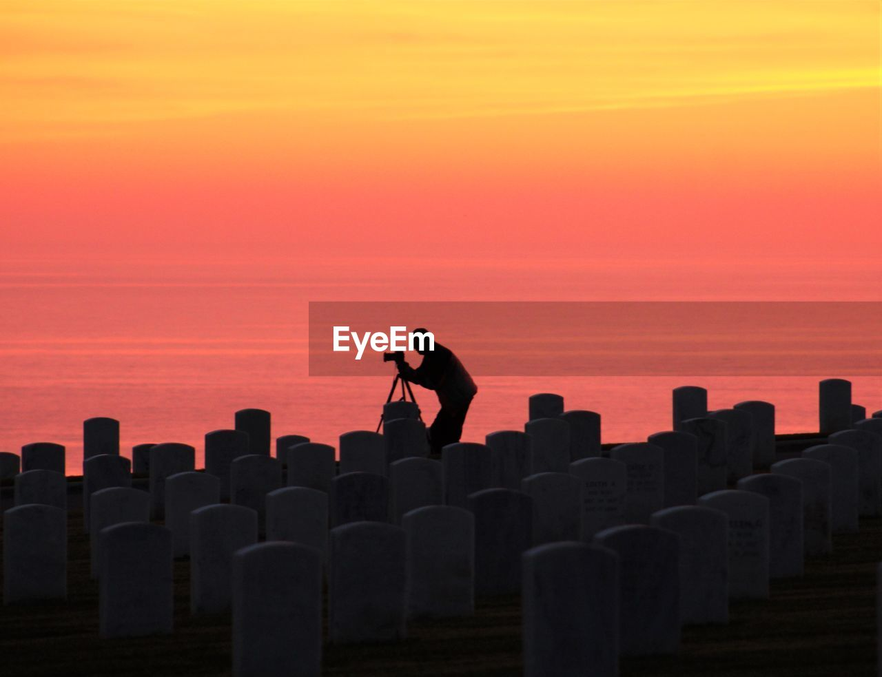 Silhouette Man Photographing By Tombstones At Fort Rosecrans National Cemetery