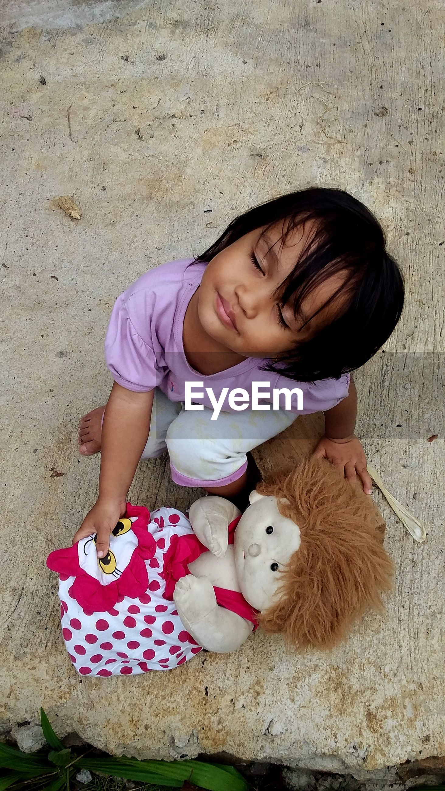 High angle view of girl with eyes closed holding toy